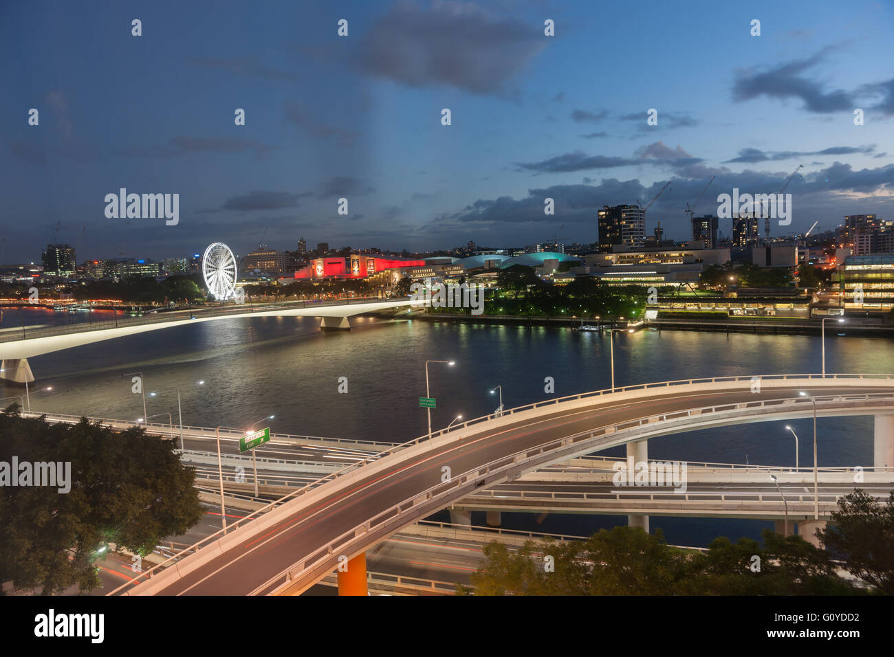Brisbane night lights over tiered roadways river and South Bank buildings and giant ferris wheel - Stock Image