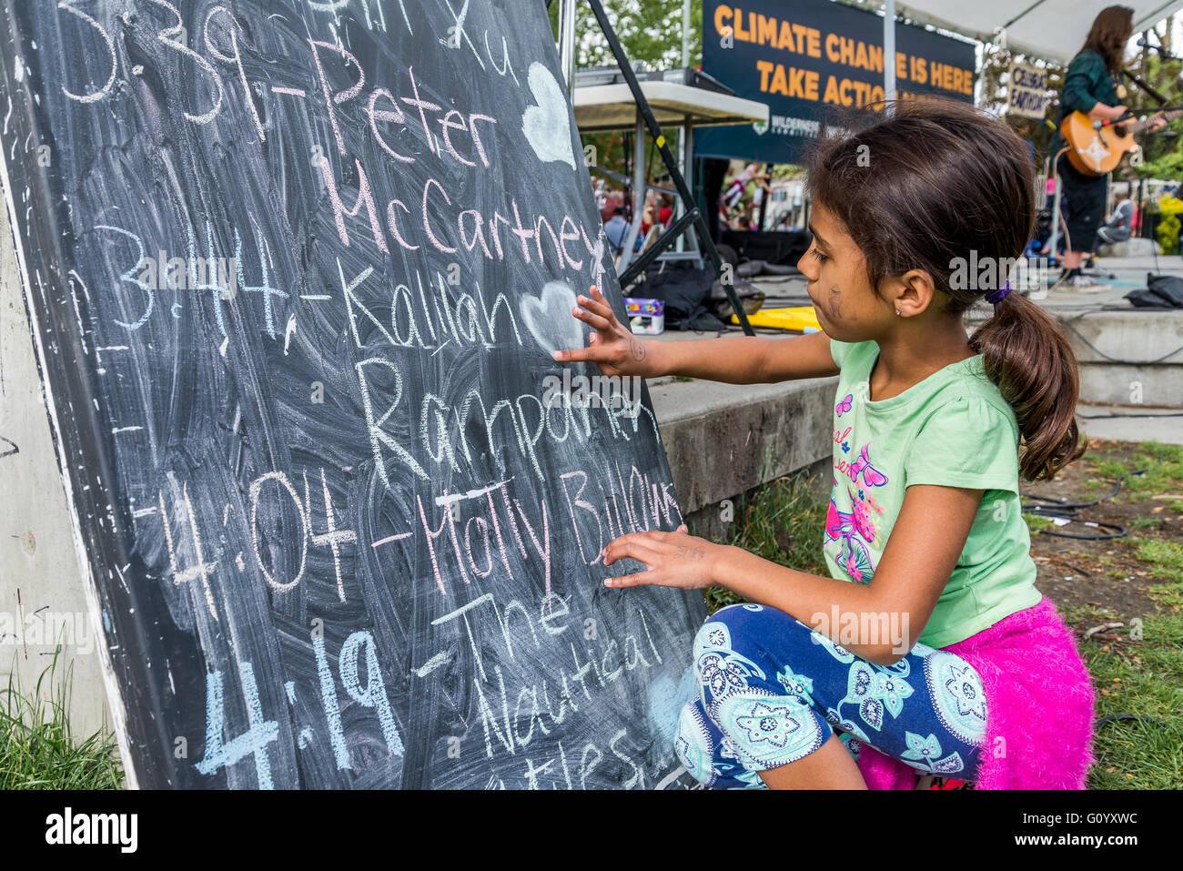 Young  girl drawing heart on chalkboard. - Stock Image