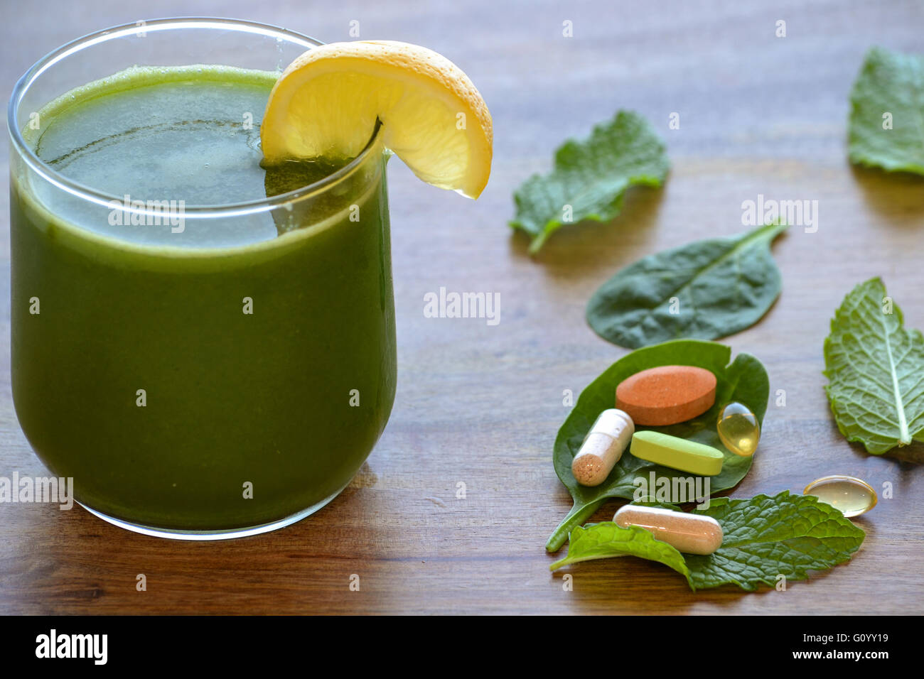 Green detox smoothie and dietary supplements on wooden table - Stock Image