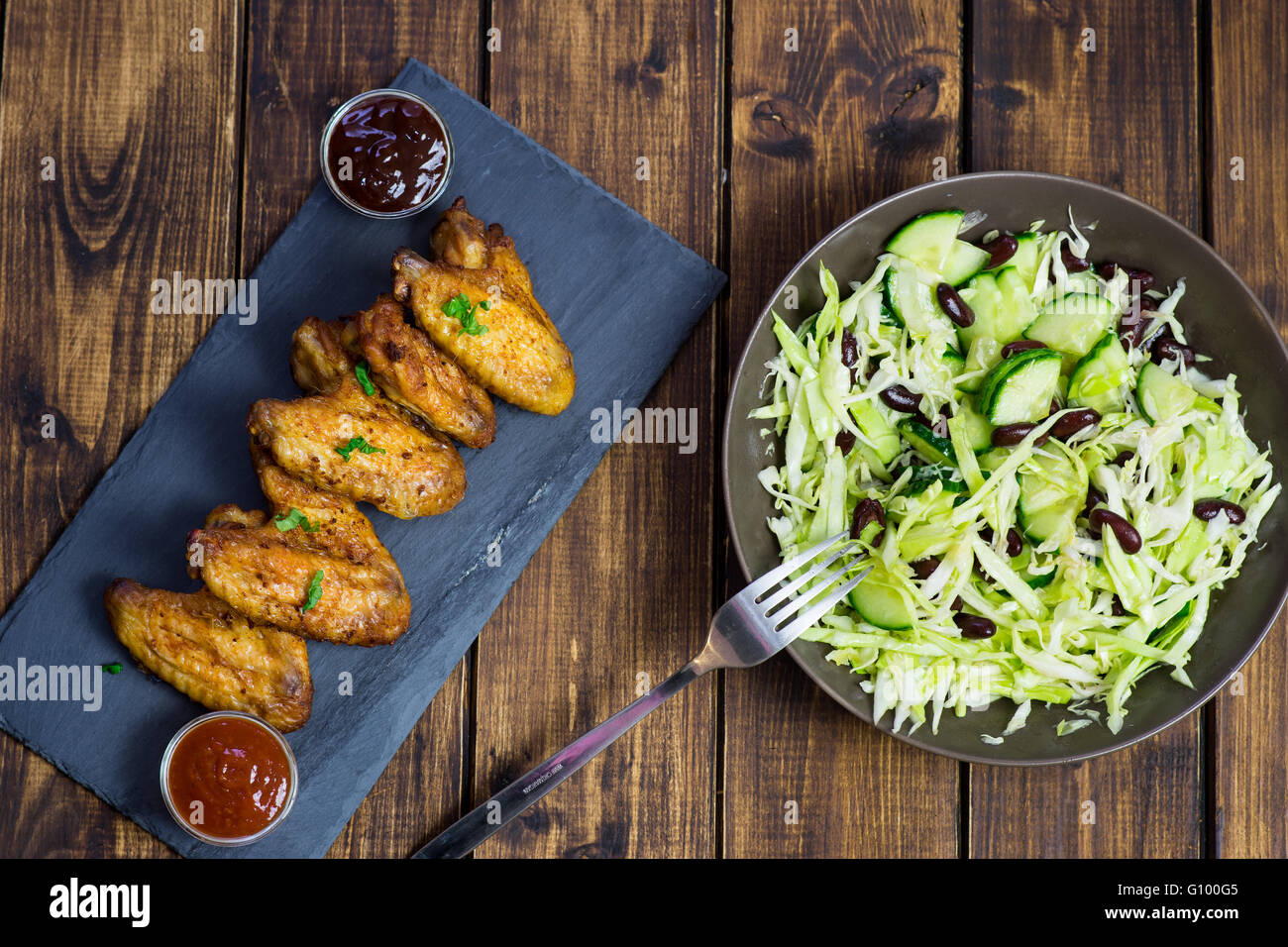 Chicken wings on a slate plate and salad on wooden background Stock Photo
