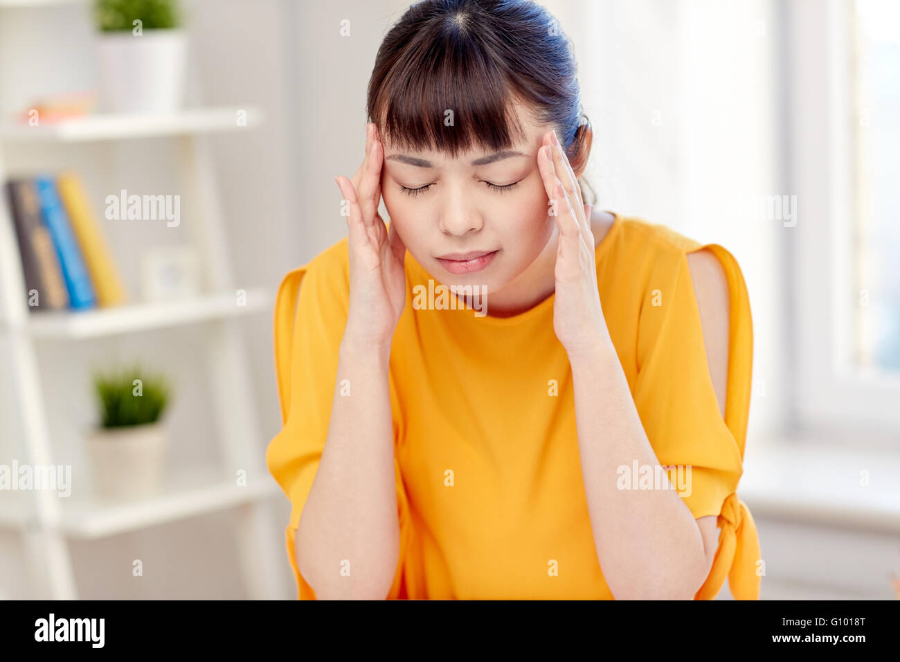 tired asian woman suffering from headache at home - Stock Image