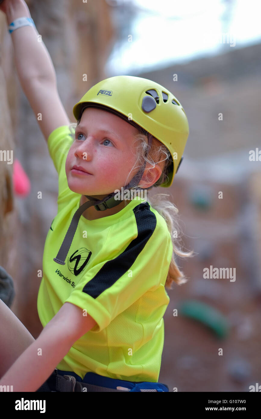 A young girl climbing at an indoor climbing centre wall - Stock Image
