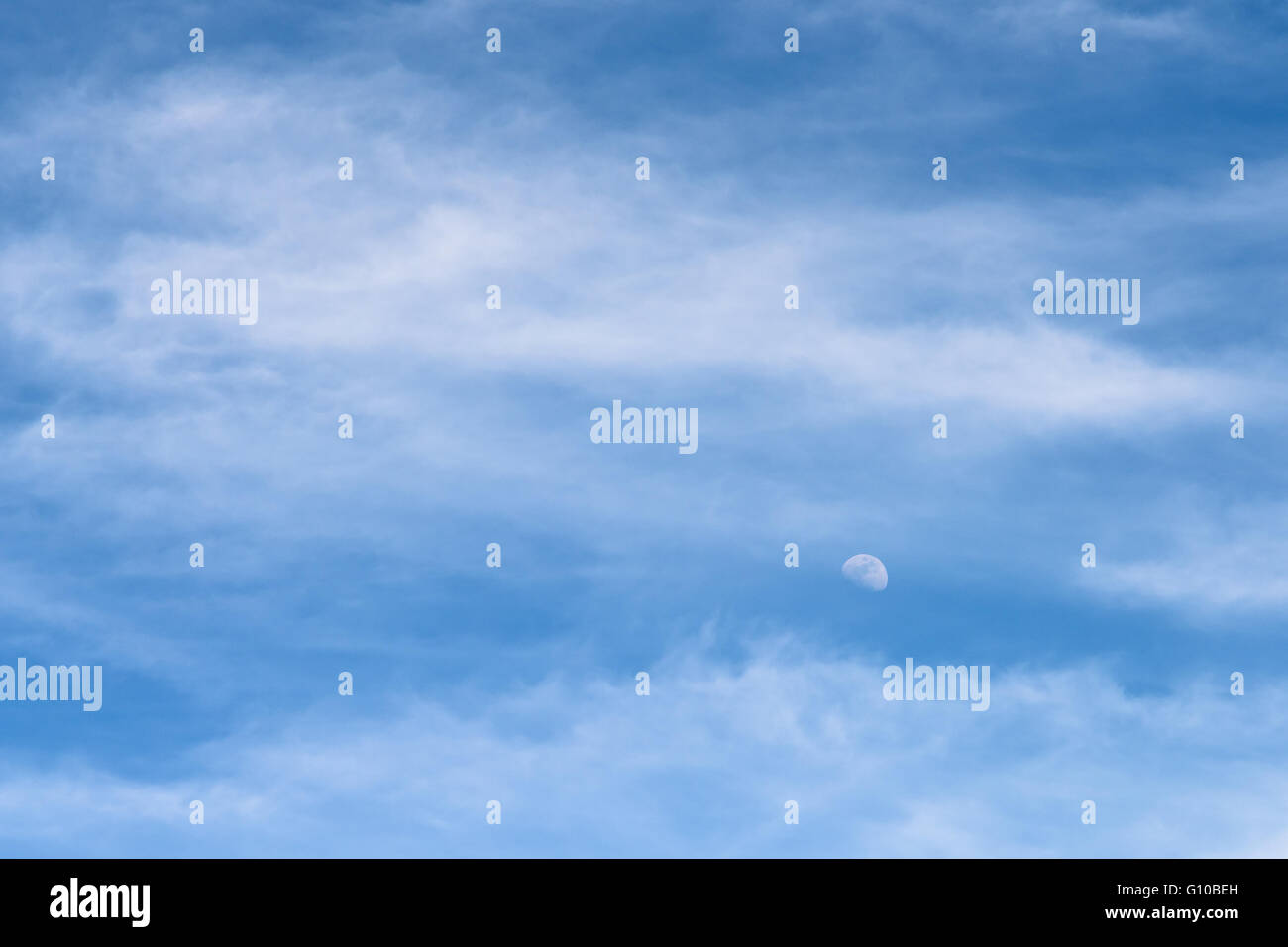 moon visible in daylight blue sky with white soft clouds stock photo