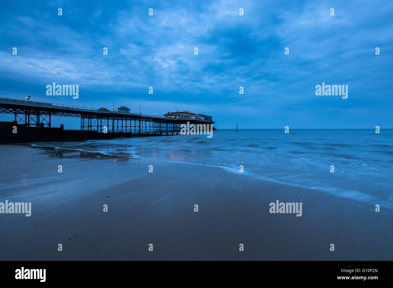 Cloudy evening at Cromer Pier, Norfolk as the sun sets - Stock Image