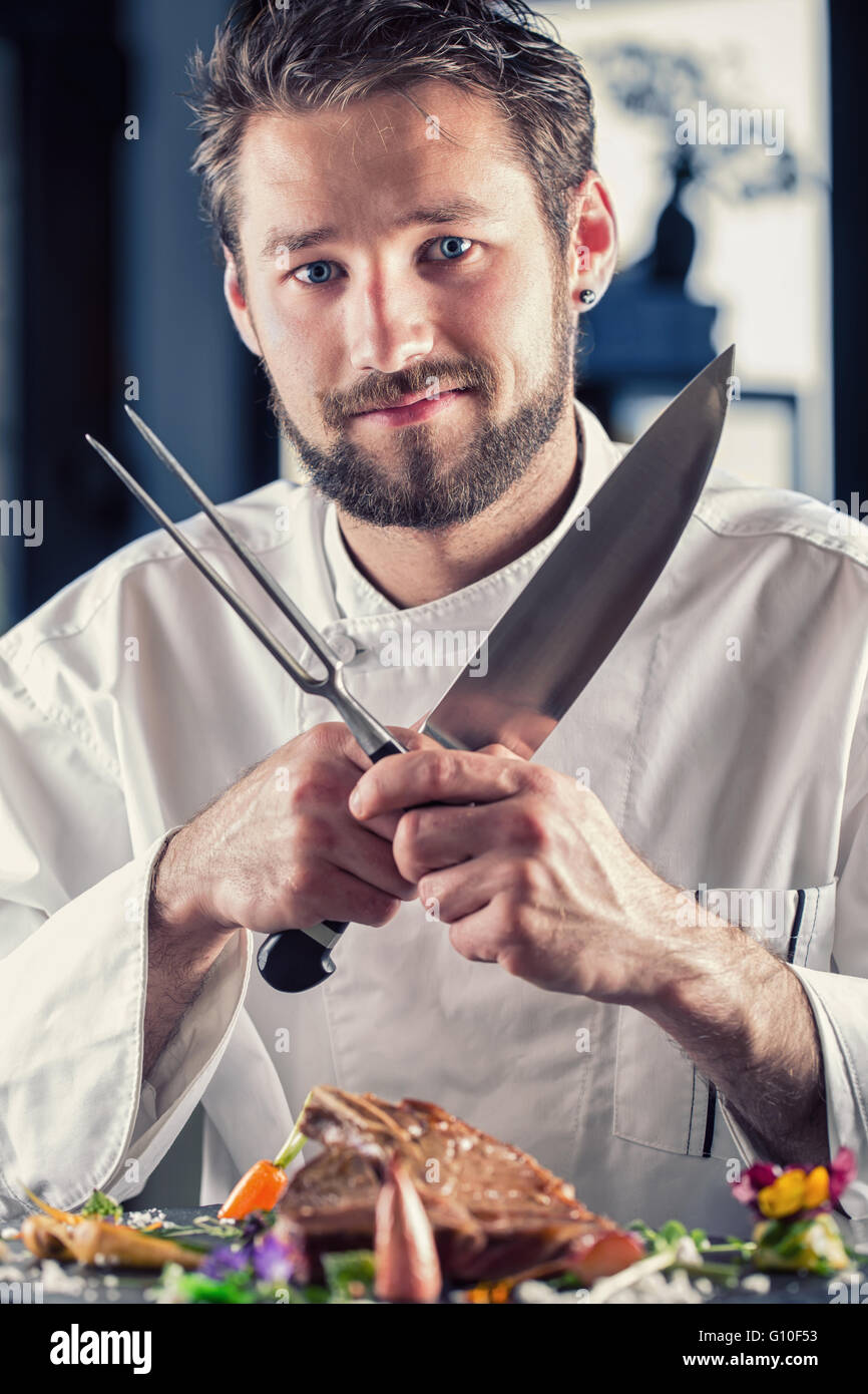 Chef in hotel or restaurant kitchen cooking, only hands. He is working on the micro herb decoration. - Stock Image