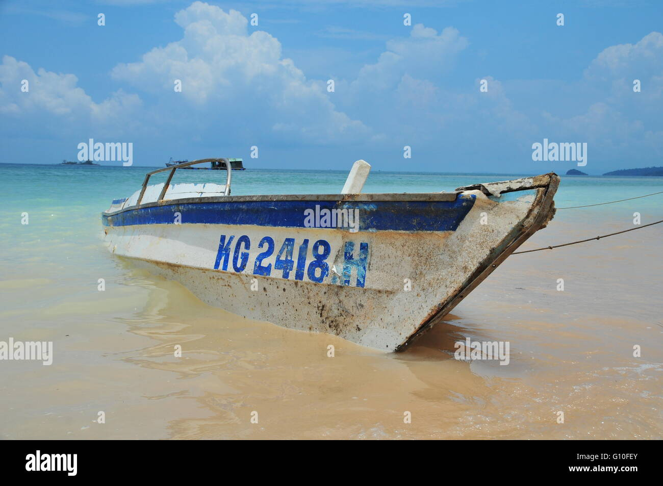 Wood boat washed ashore on Phu Quoc Beach, Vietnam - Stock Image