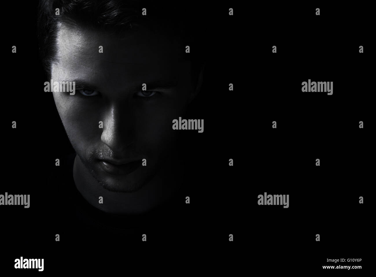dark young adult man portrait fade in black - Stock Image