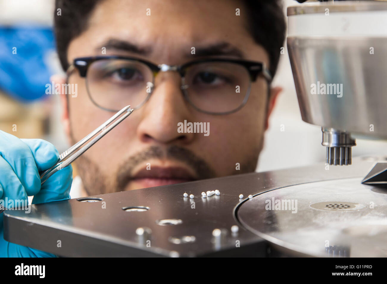 Research at the Institute of Pharmaceutics and Biopharmaceutics. Doctoral student at the tablet press machine. - Stock Image