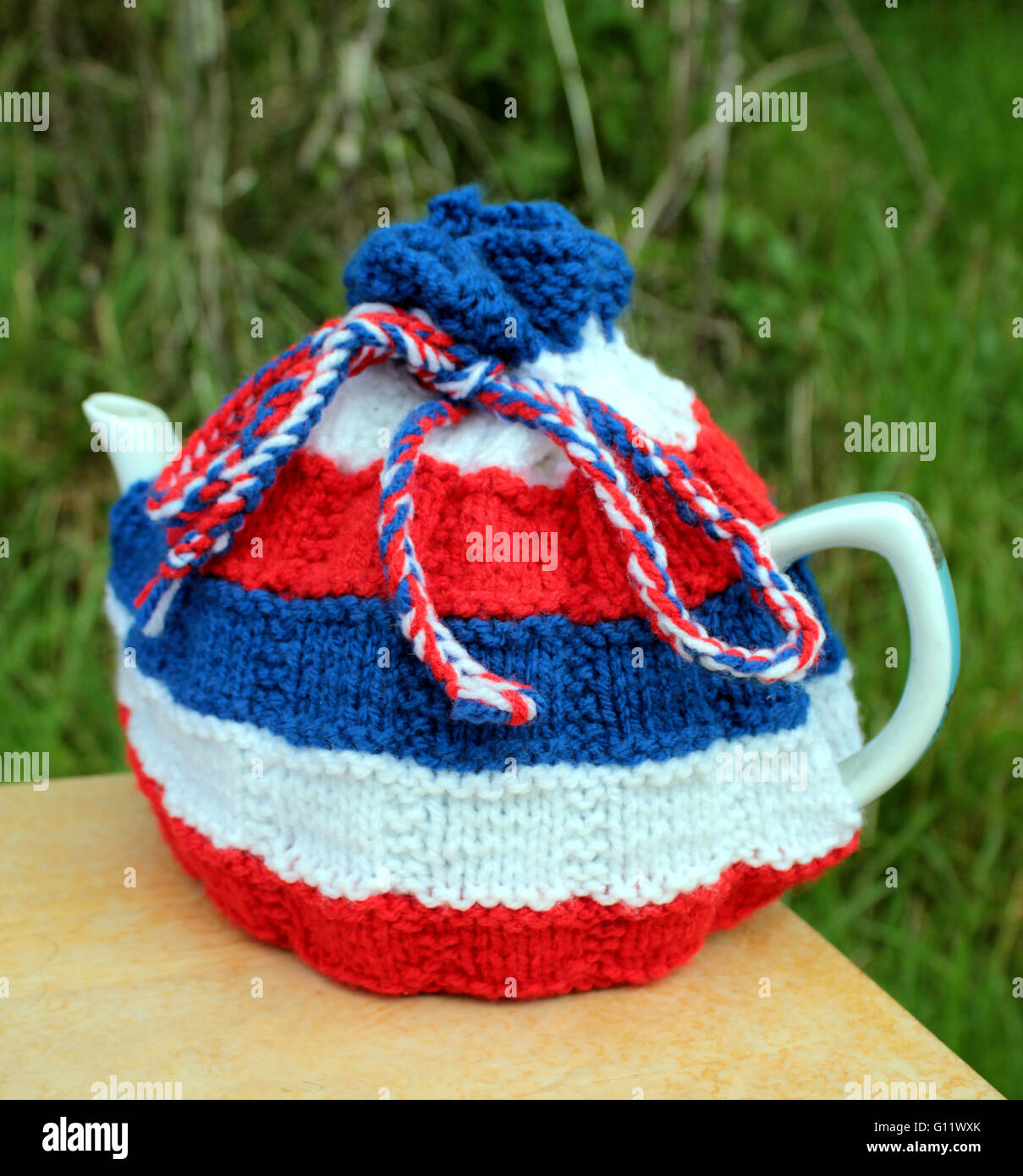 Hand knitted tea cosy in Red White and Blue yarn, could be patriotic for the UK or USA. - Stock Image