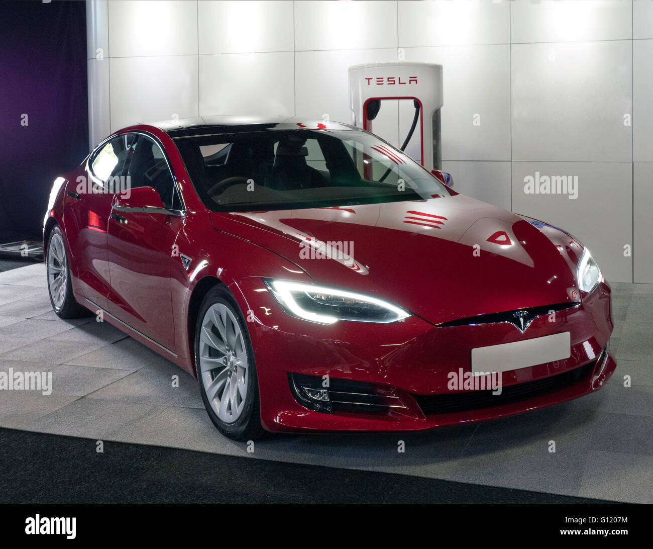 Tesla Electric automobile on charge at Tesla charging point - Stock Image