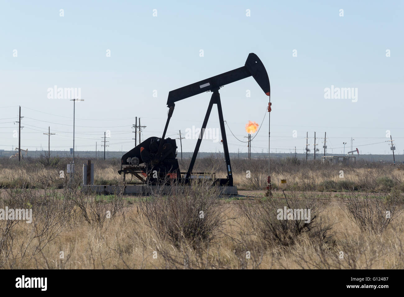 Powerlines, gas flarring and pump jacks in West Texas. - Stock Image