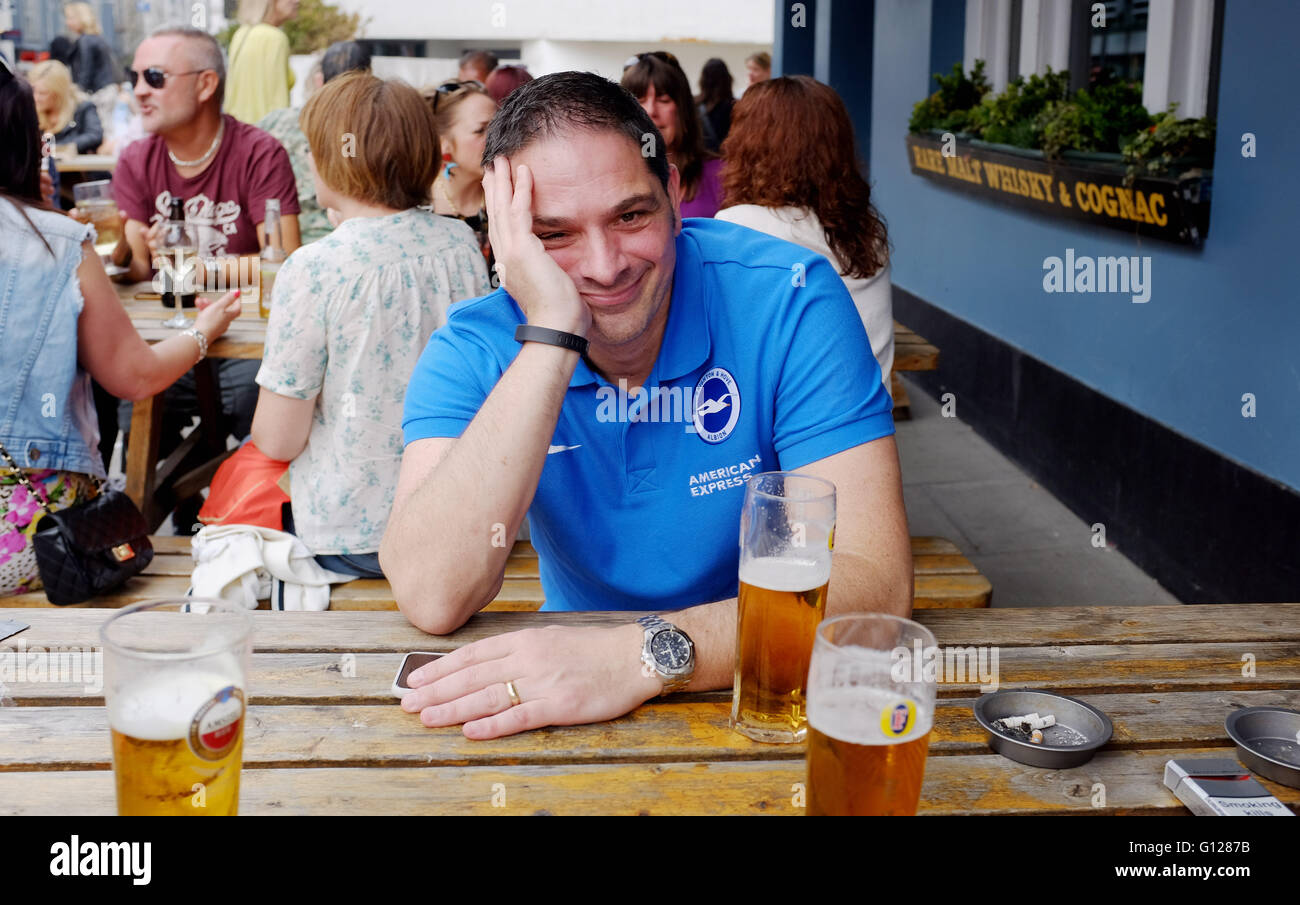 Brighton football fan drowning his sorrows after they drew against Middlesbrough and now have to get promotion via - Stock Image