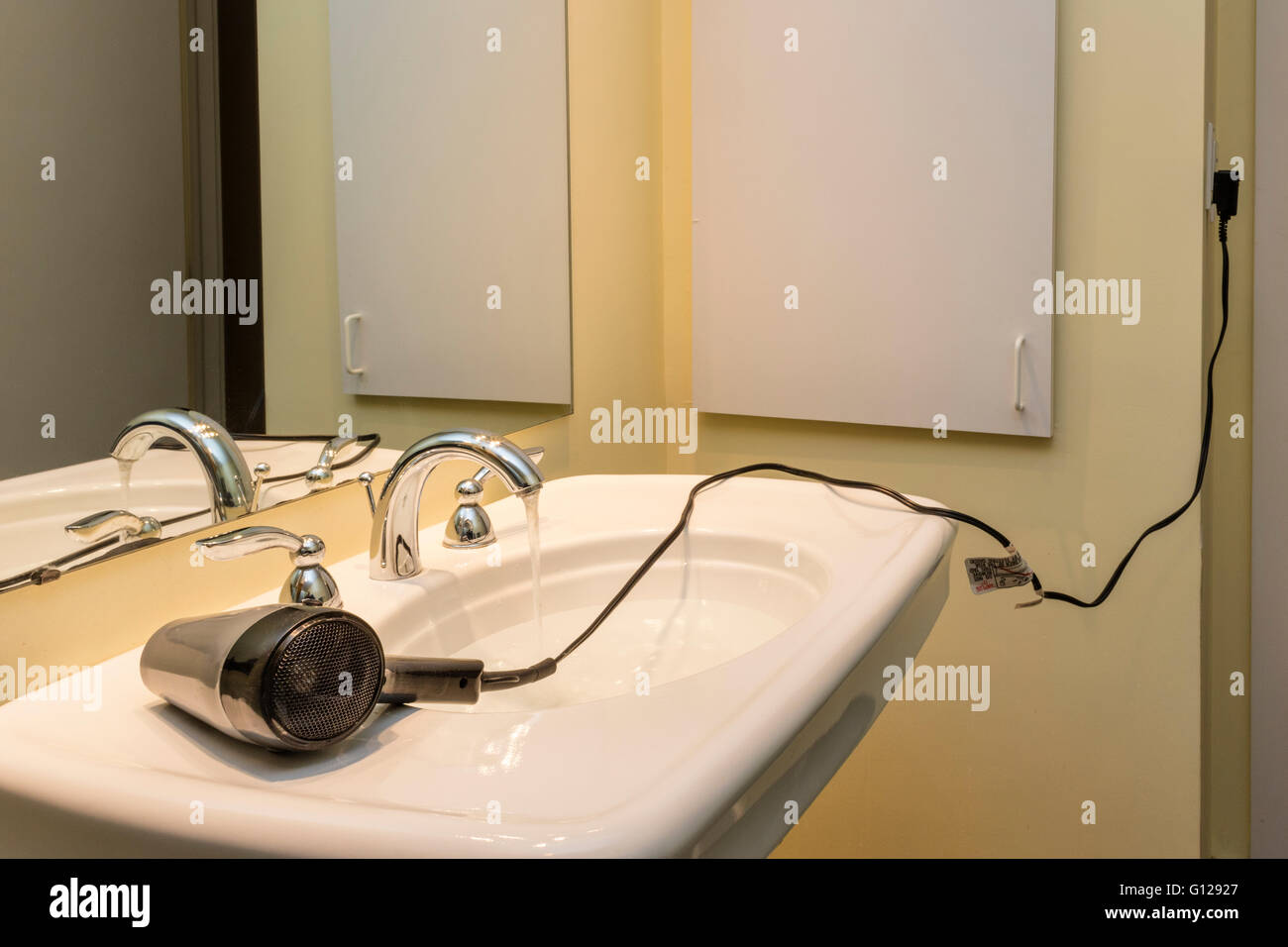 Hair dryer with electric cord stretching across sink, posing shock or electrocution risk. Suitable for OT safety - Stock Image