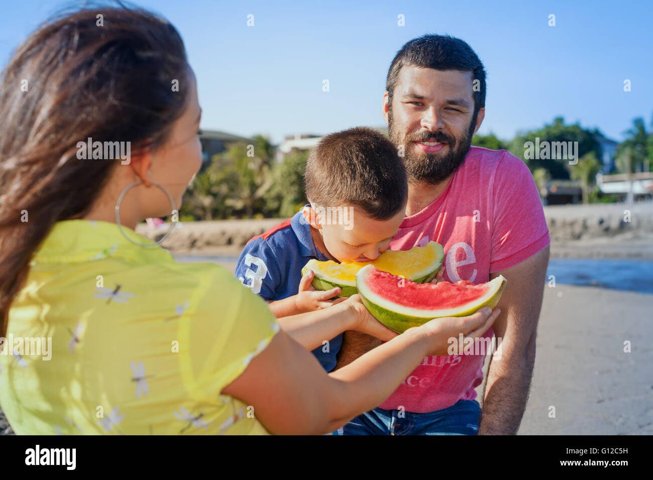Happy family funny picnic on morning sea beach - mother feed baby boy, adult man. Father, son eat fruits with fun. Stock Photo