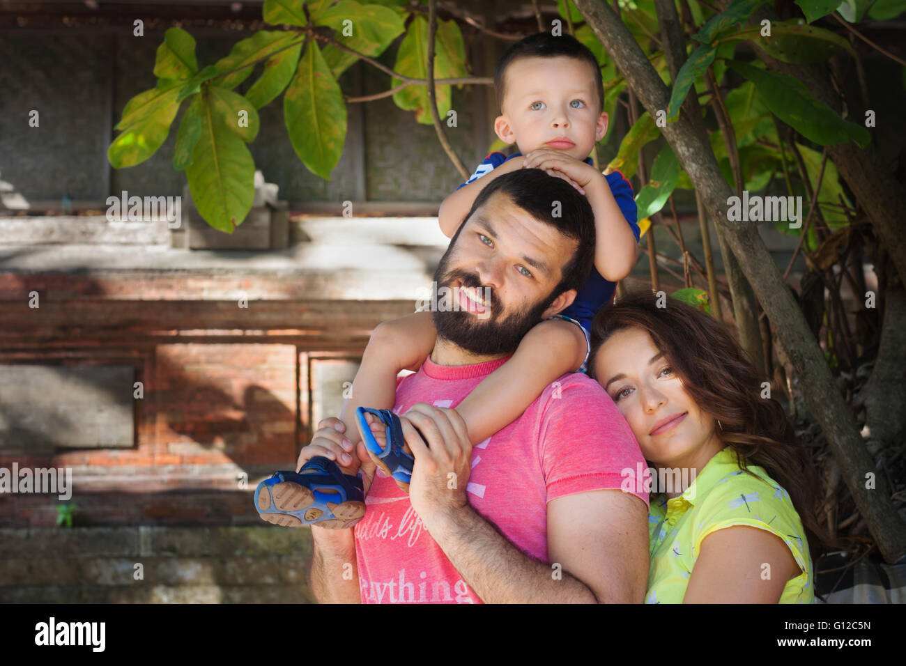 Face portrait of beautiful family - happy mother, father holding baby son on shoulders walk with fun. - Stock Image