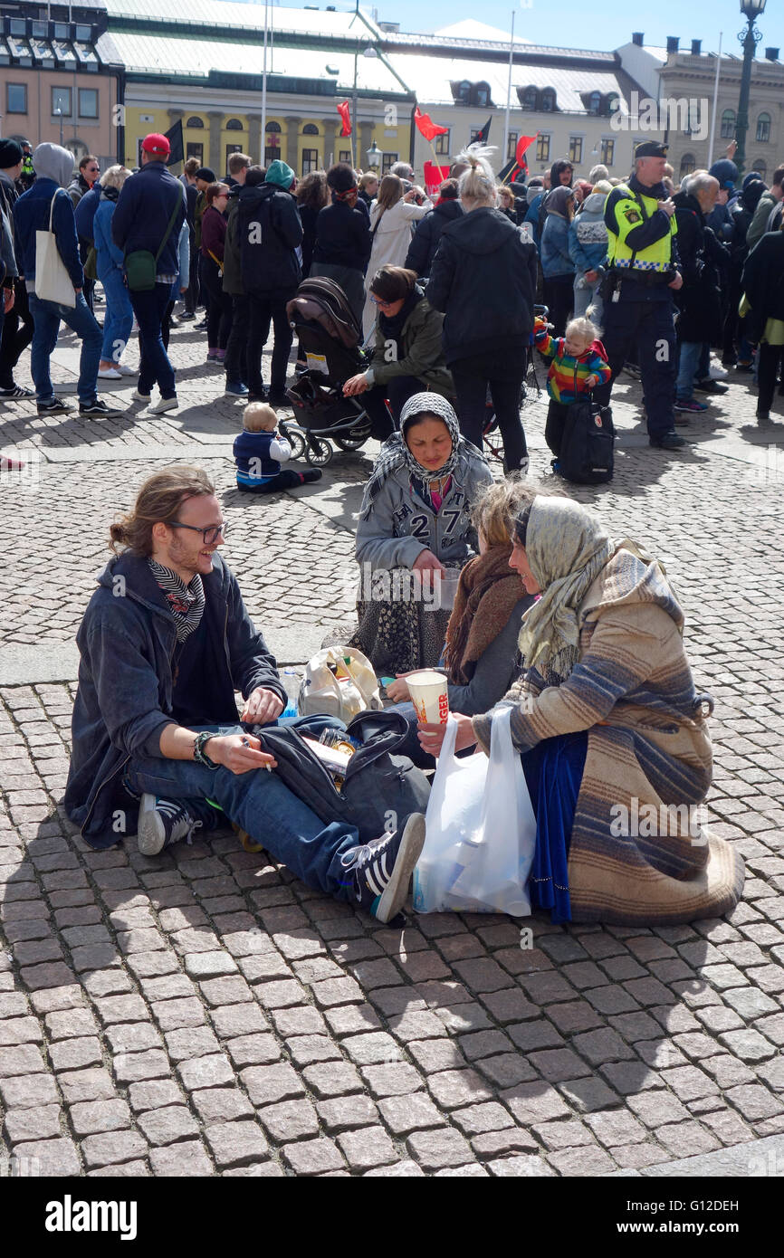 Two woman involved in Aggressive panhandling approach a young couple and beg for donations. Gothenburg, Sweden. - Stock Image