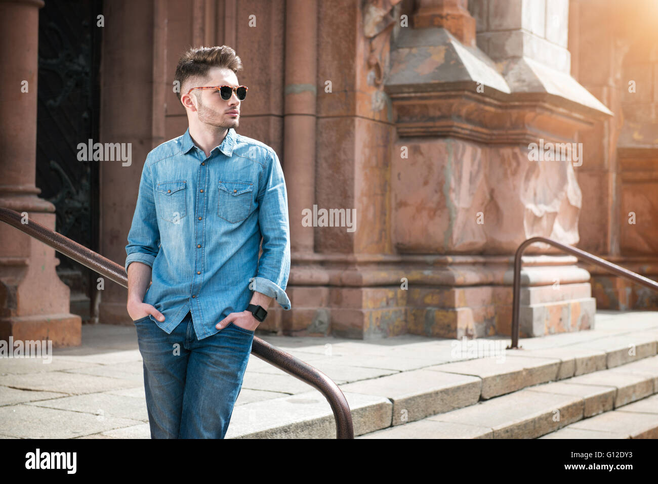 Confident guy leaning on the handrail - Stock Image