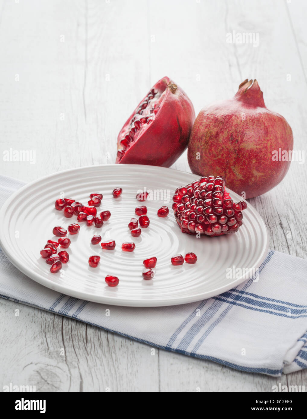 Pomegranate whole, half and seeds on white plate. Vertical image with back lighting. Shallow depth of field. - Stock Image