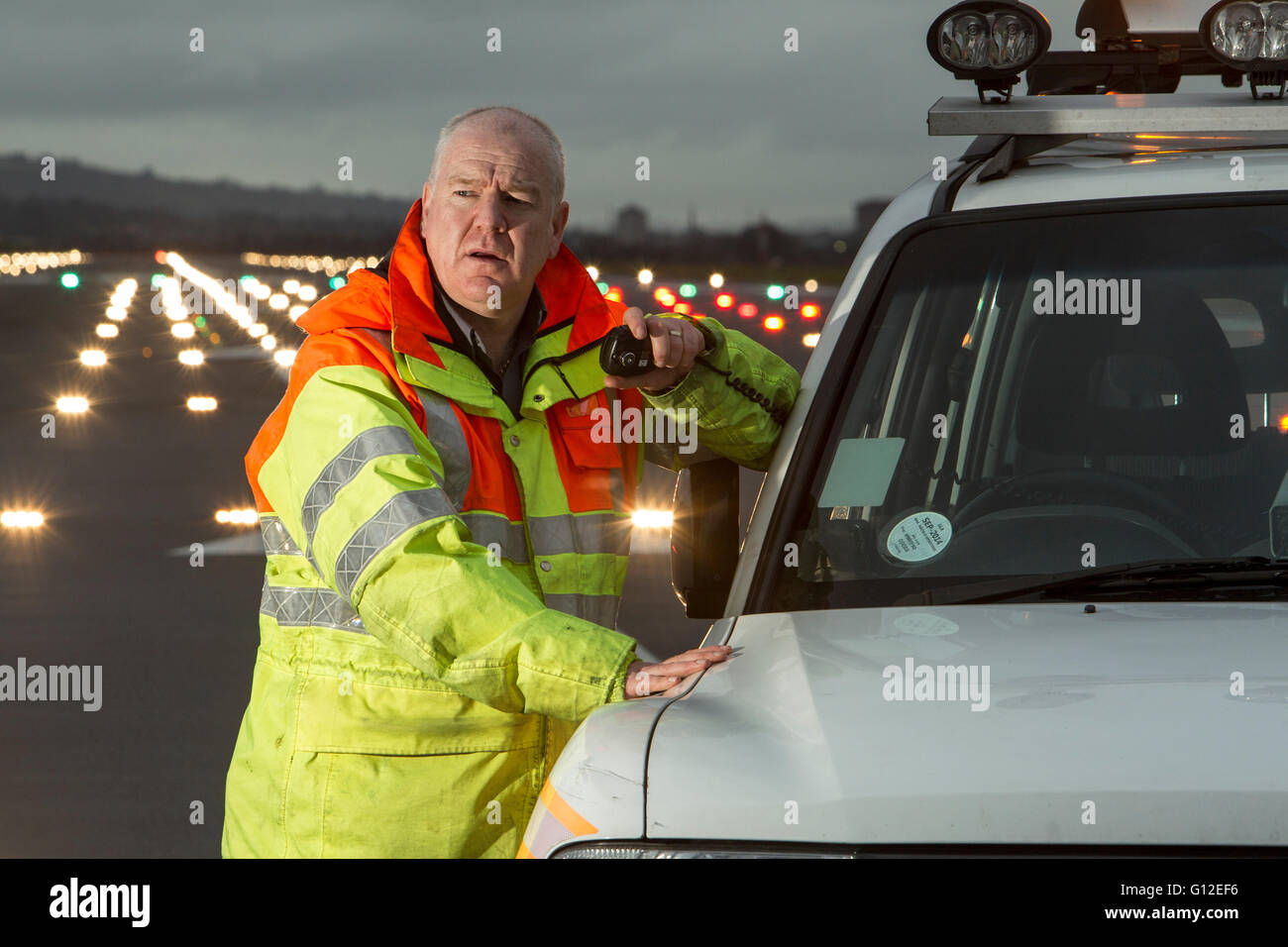 Ground Crew on runway at Glasgow Airport with landing lights in background - Stock Image