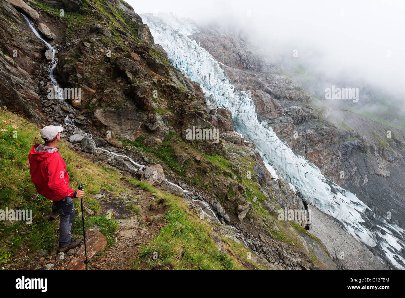 Europe, Switzerland, Bernese Oberland, Interlaken, Grindelwald, hiker on trail above Gletscher glacier - Stock Image
