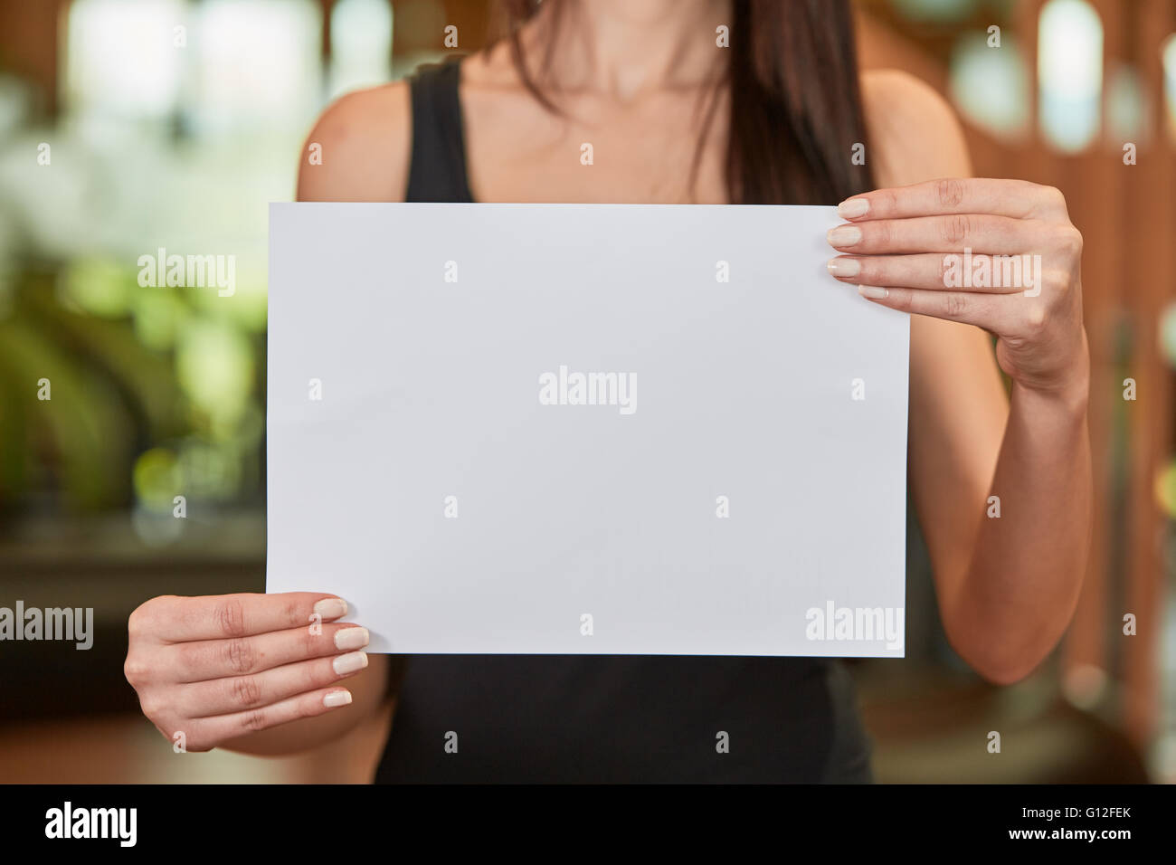 Young caucasian woman holding white sheet of paper - Stock Image