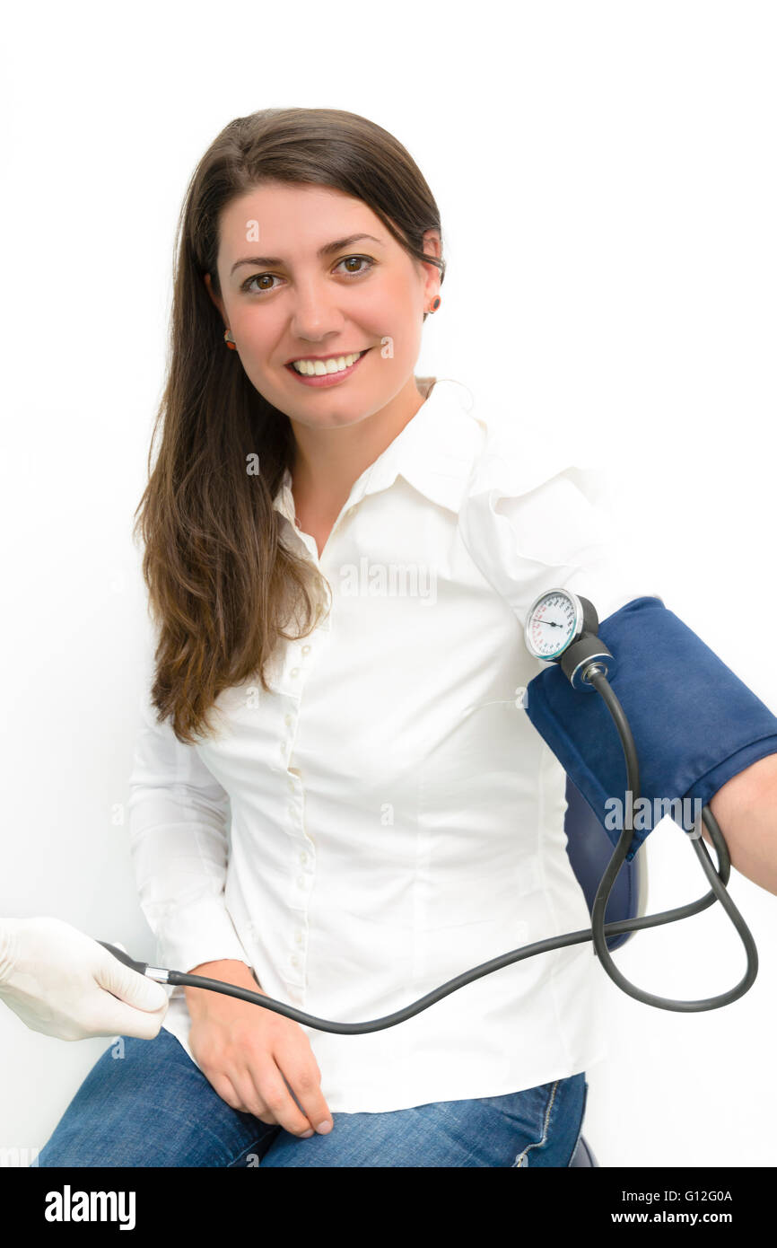Beautiful young woman using blood pressure measurement device sphygmomanometer - Stock Image