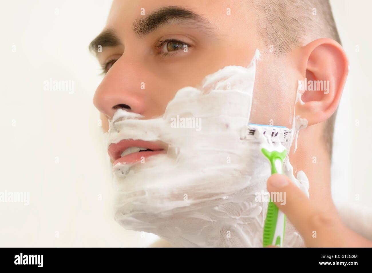 Young man shaving using shaving blade - Stock Image