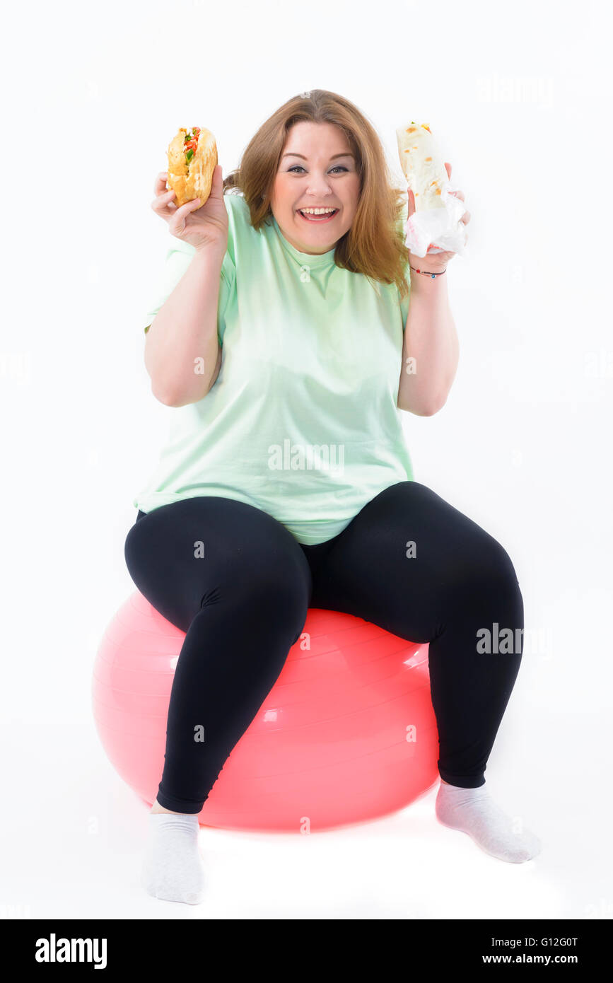 Corpulent woman having addiction to unhealthy food sitting on fitness ball - Stock Image