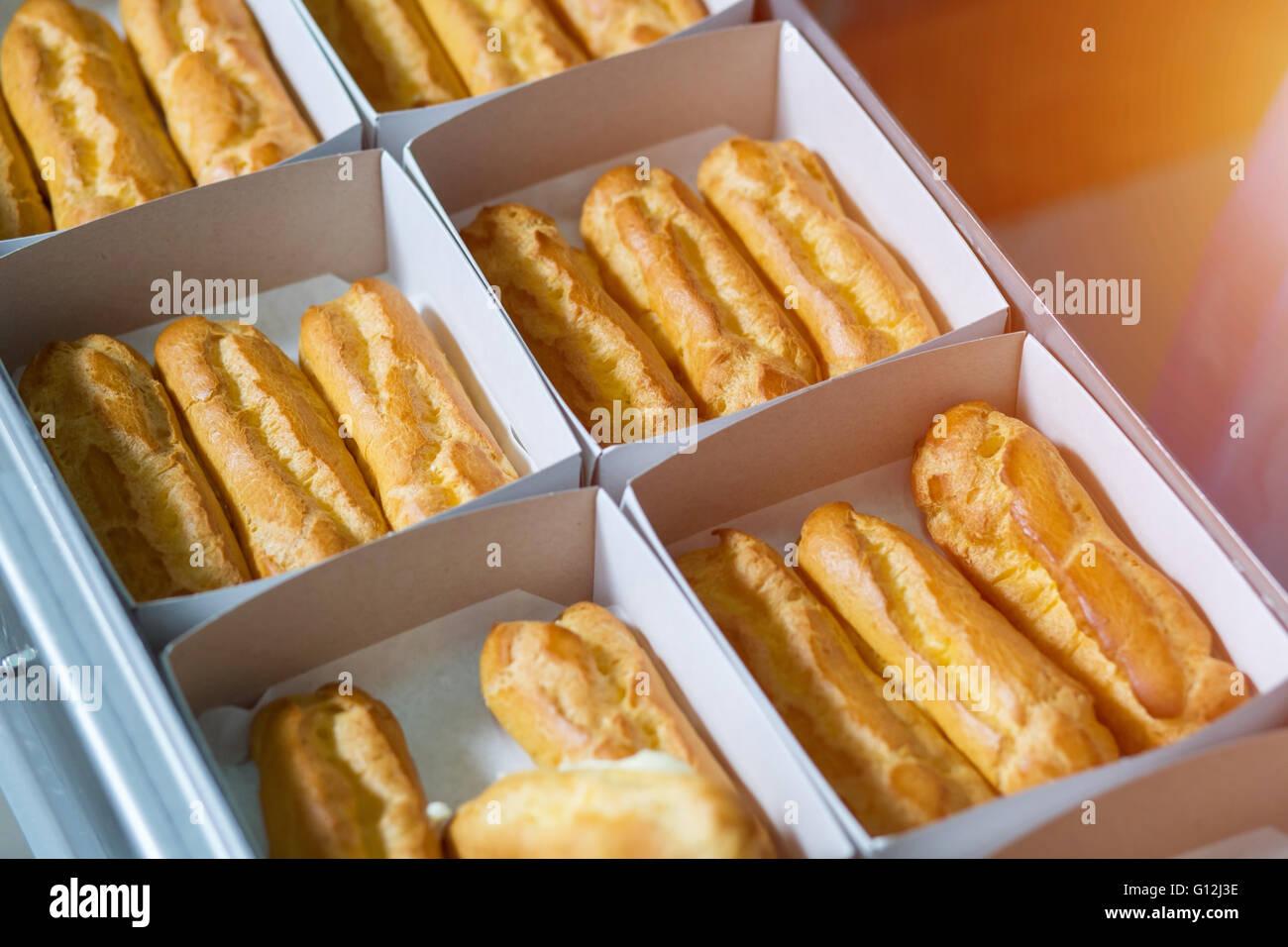 Boxes with eclairs on conveyor. - Stock Image