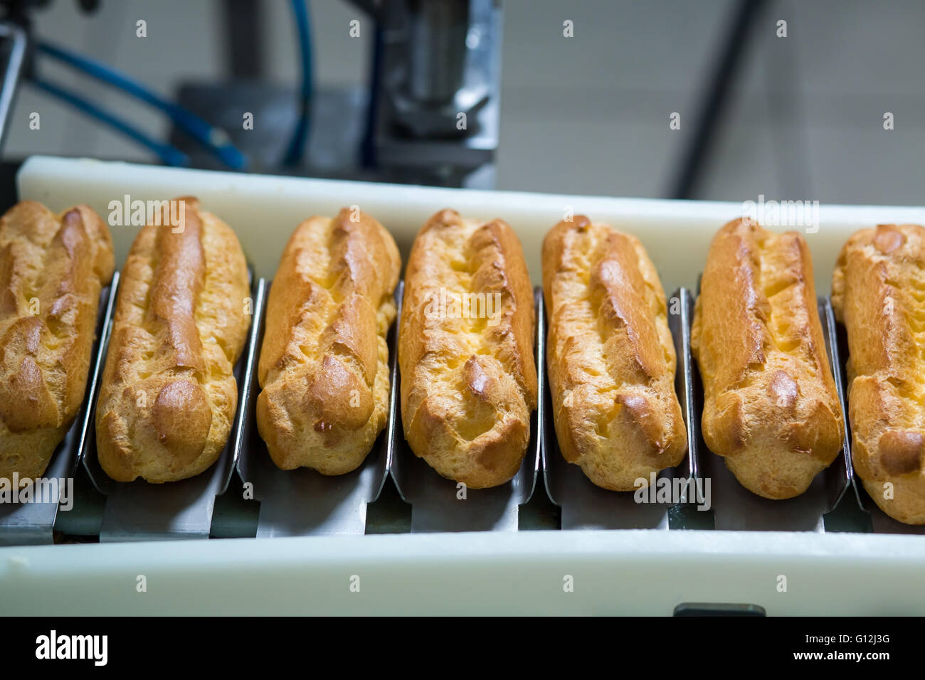 Conveyor line with eclairs. - Stock Image