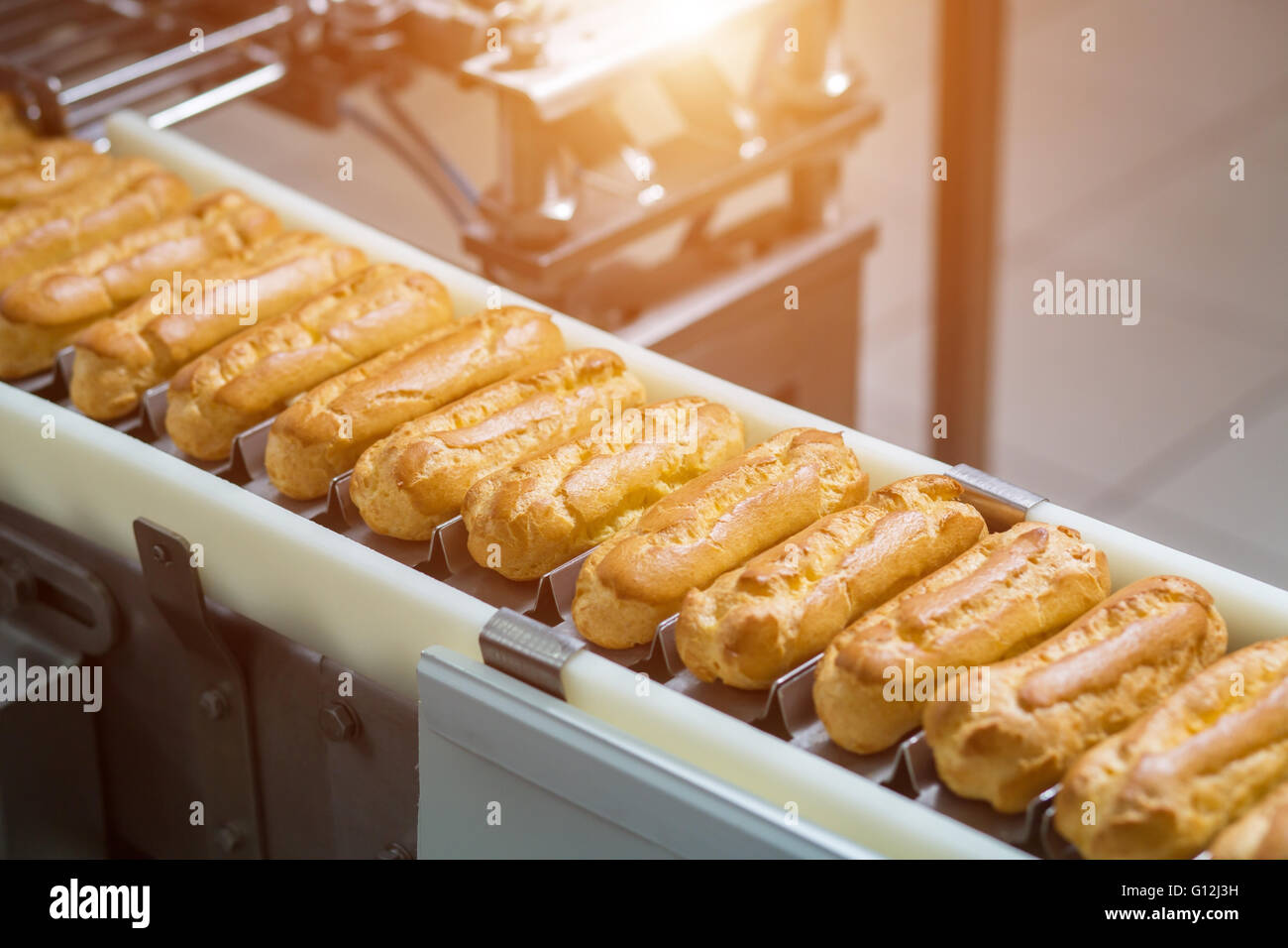 Narrow conveyor with eclairs. - Stock Image