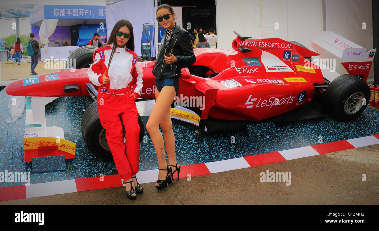 Chinese models posing in front of race car in car exhibition at Shanghai formula one, China 2016. - Stock Image