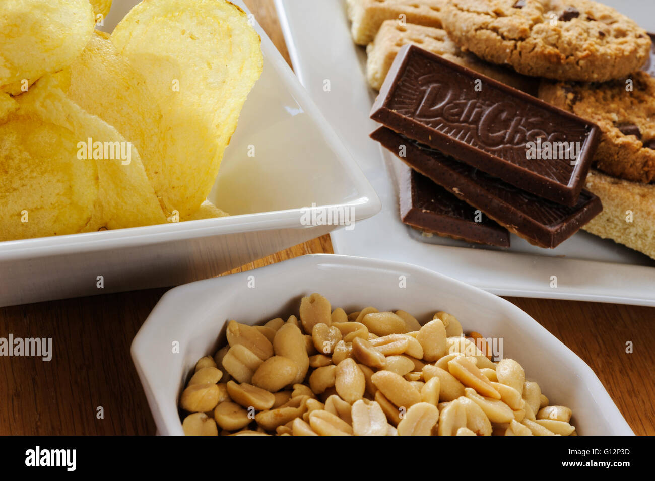 Bowls of peanuts, crisps and biscuits. - Stock Image