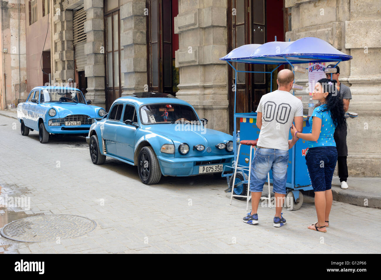 An icecream seller parks up next to two blue classic cars in Old ...