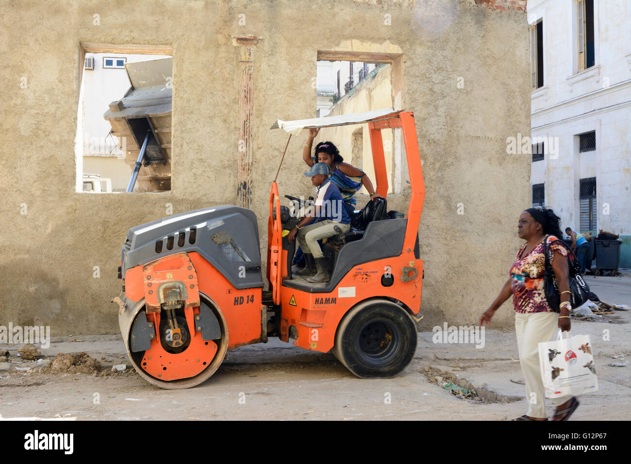A mother teaches her young son how to drive a road roller in Central Havana, Havana, Cuba - Stock Image