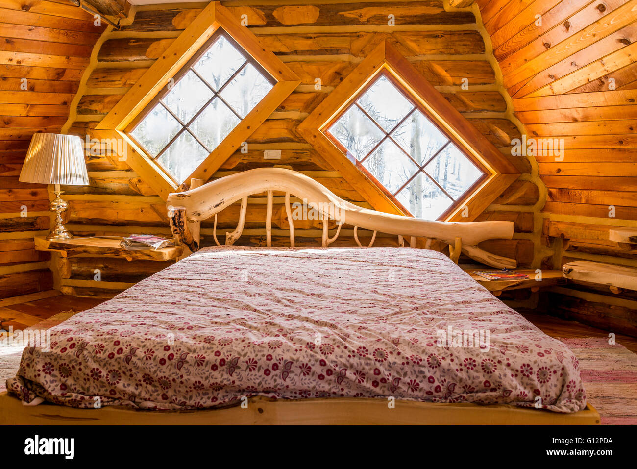 Handmade bed in funky log cabin - Stock Image