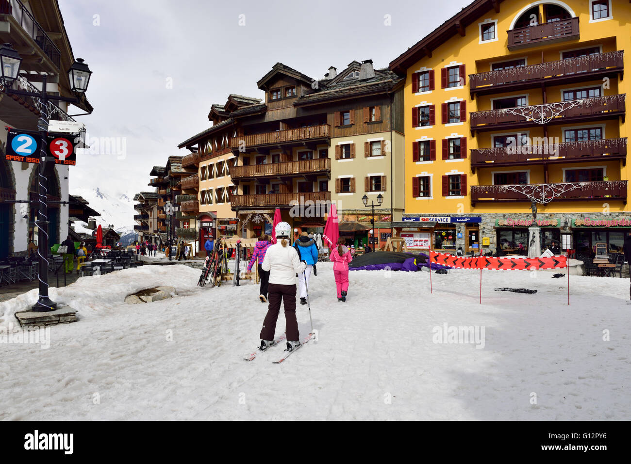 Skiing and walking into the French resort of Les Arcs 1950 in the Alps - Stock Image