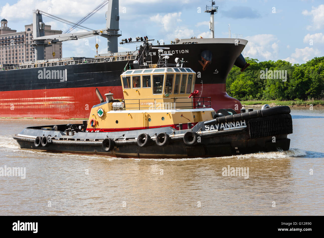 Tugboat 'Savannah' leads bulk carrier ship 'New Direction' along the Savannah River in Savannah, - Stock Image