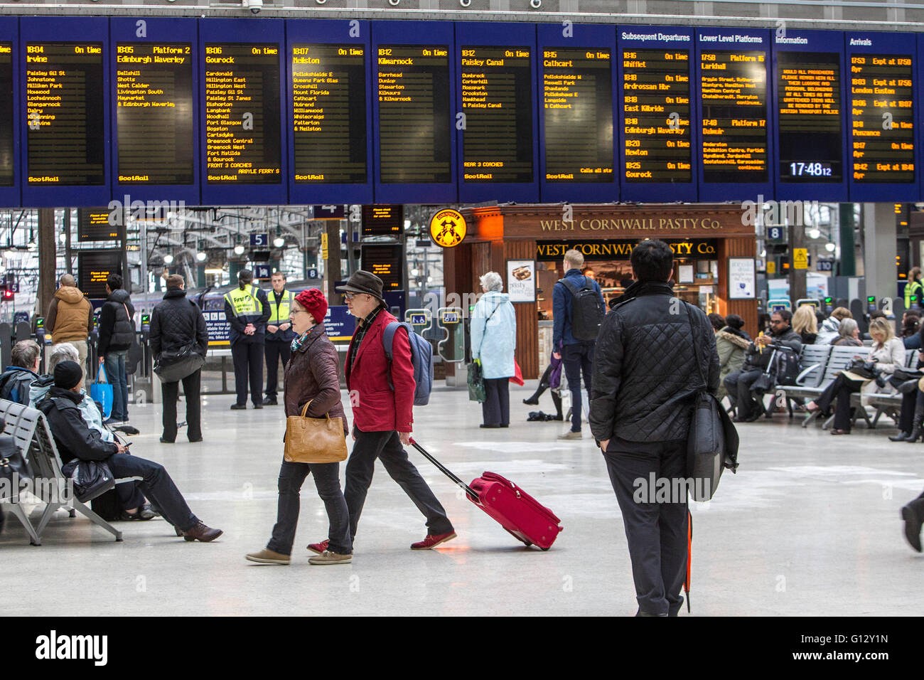 Commuters at Central Station Glasgow with destination board in background - Stock Image