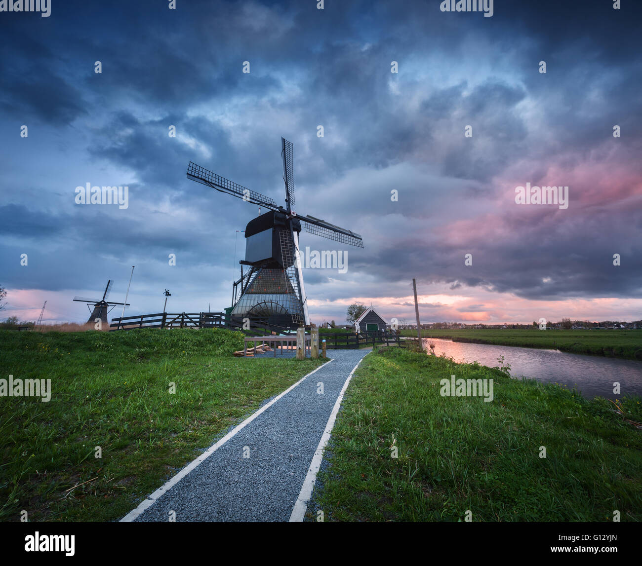 Beautiful landscape with traditional dutch windmills near the famous water canals with dramatic sky, colorful clouds Stock Photo