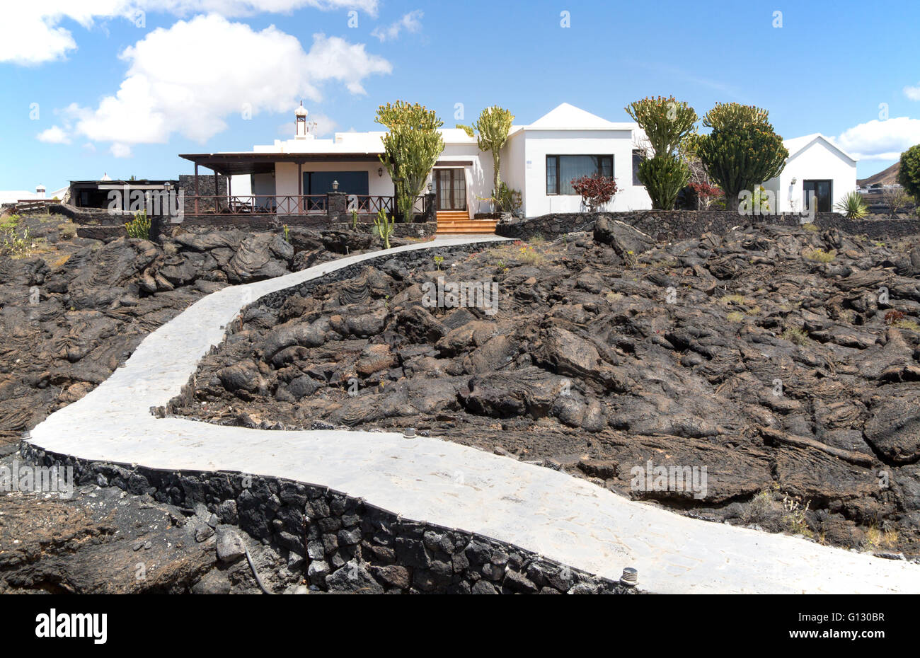 Garden path crossing solidified pahoehoe or ropey lava field to house, Tahiche, Lanzarote, Canary Islands, Spain - Stock Image