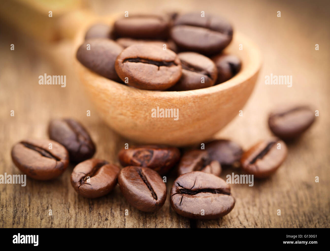 Roasted coffee bean in wooden surface - Stock Image