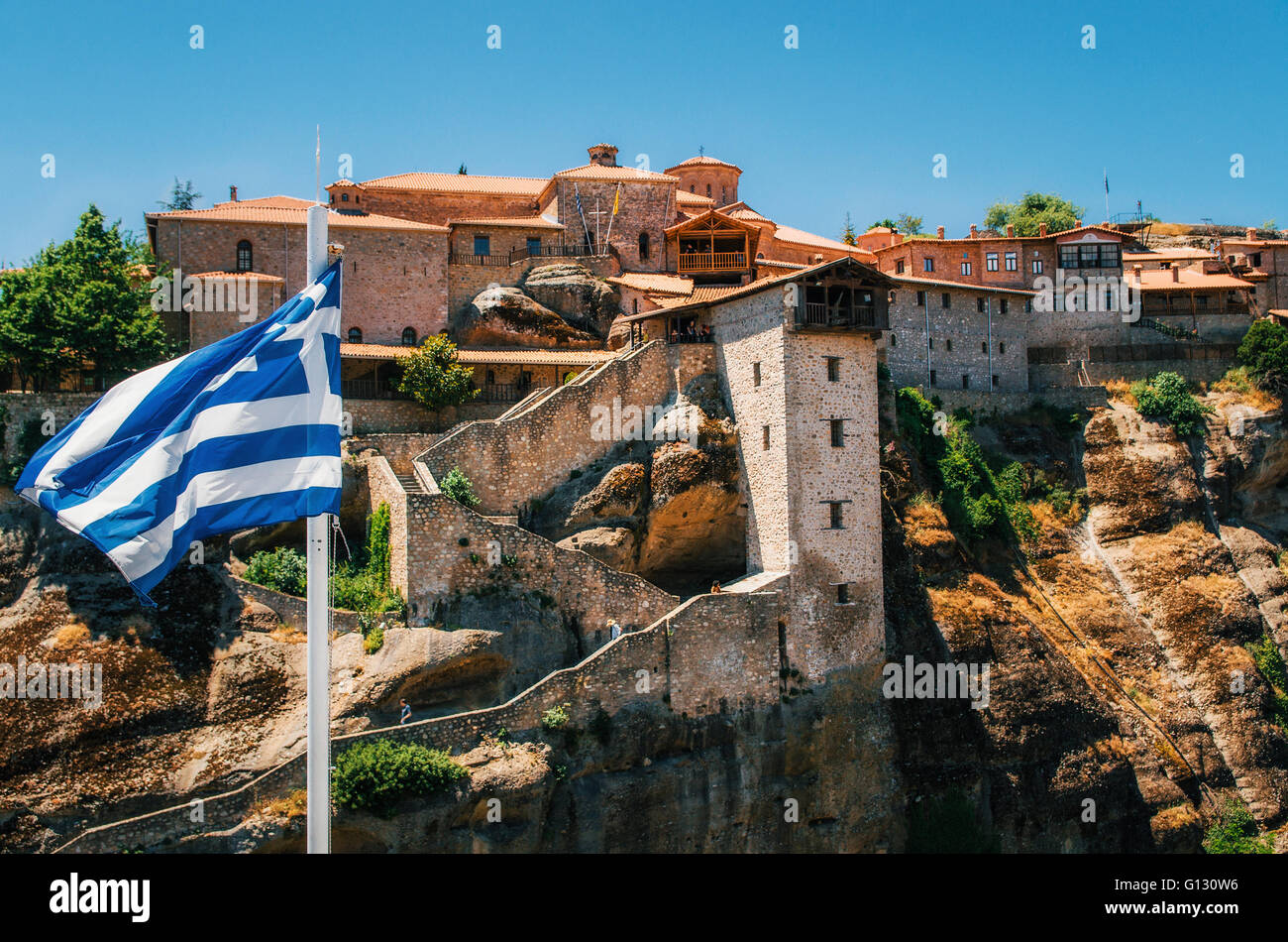 Greek flag in front of The Holy Monastery of Great Meteoron in Meteora - complex of Orthodox monasteries on mountains, - Stock Image