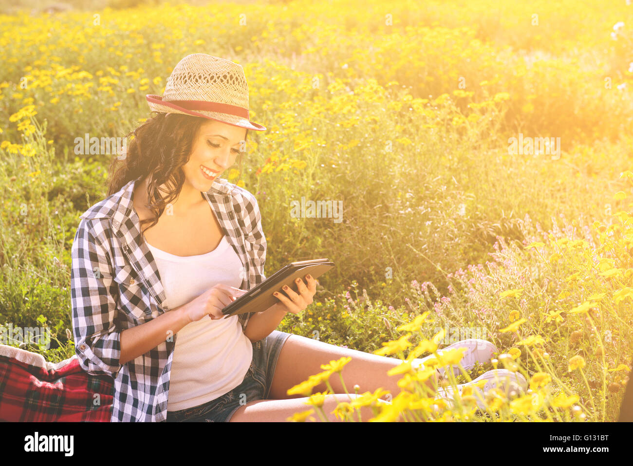 Slim girl in jeans and a T-shirt reading a book in a park sitting on a blanket - Stock Image