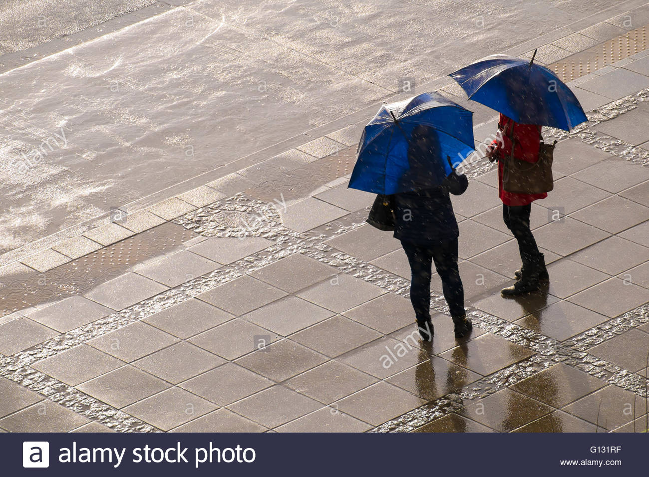 Two women with same blue open umbrellas standing on a stone pavement under rain and sun (seen from above, no faces) - Stock Image