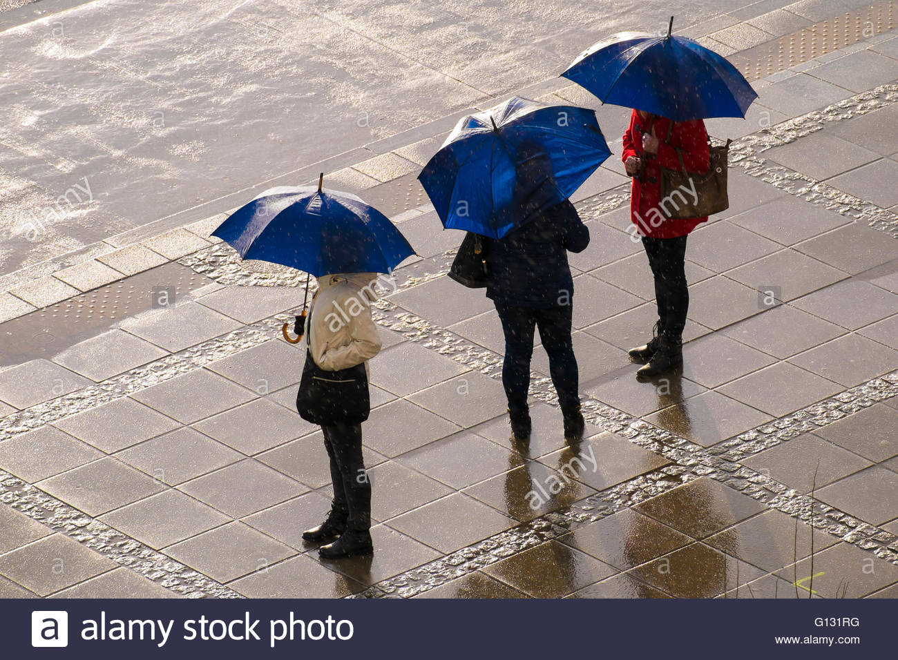 Three women with same blue open umbrellas standing on a stone pavement under rain and sun (seen from above, no faces) - Stock Image