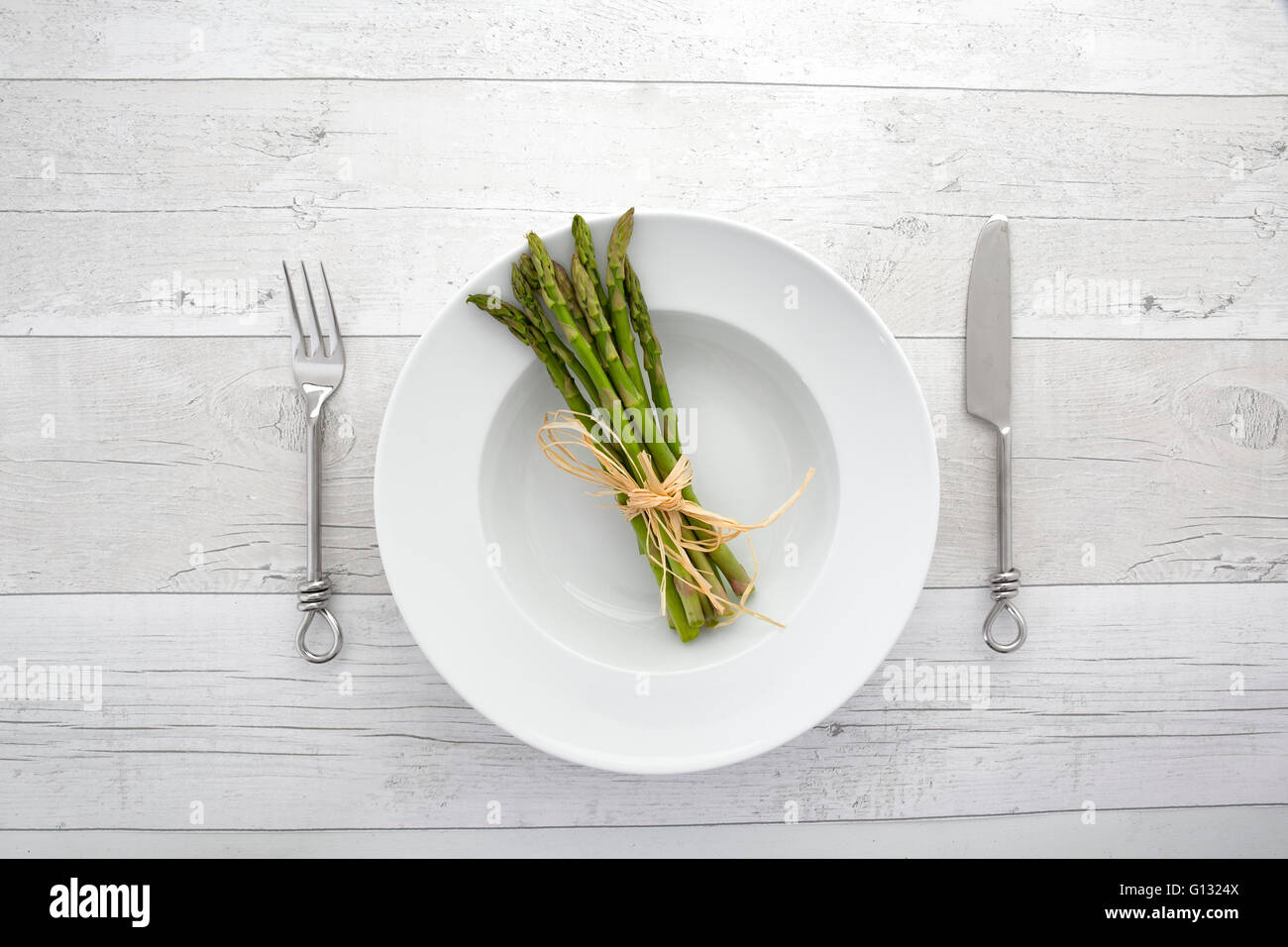 Overhead view of fresh green asparagus on a white plate over a retro wooden background - Stock Image