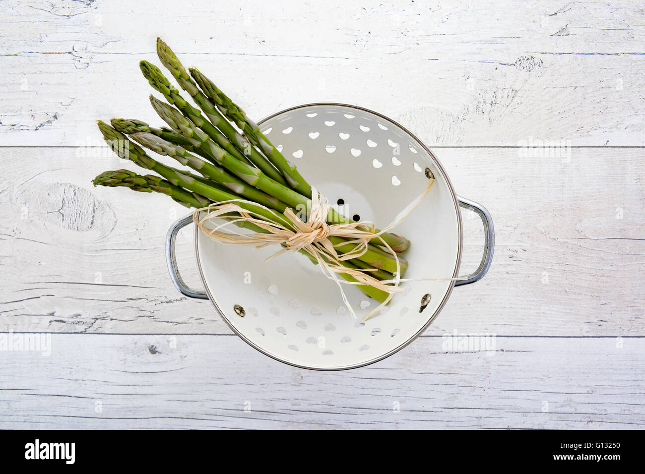 Fresh green asparagus in colander on old wooden background Stock Photo