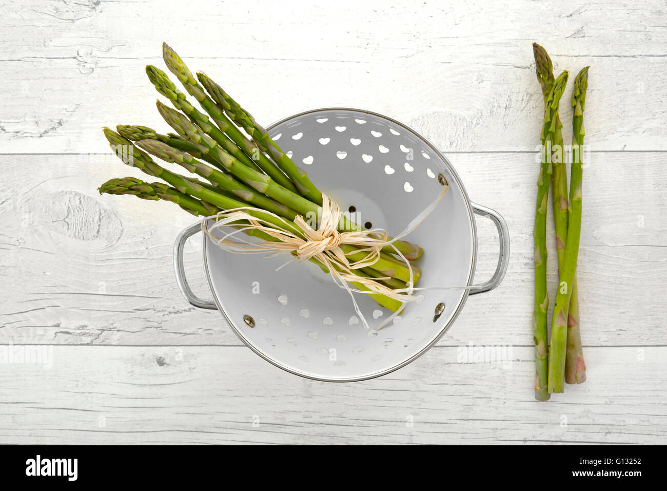 Fresh green asparagus in colander on old wooden background - Stock Image