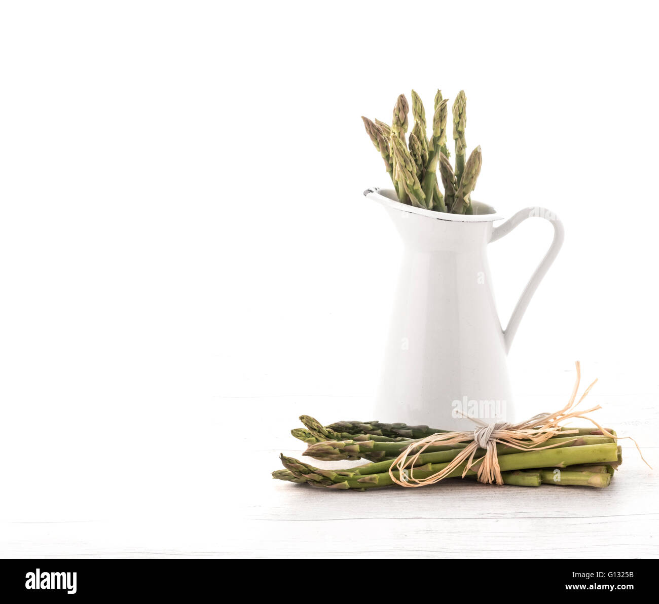 Fresh green asparagus in Jug on old white wooden background - Stock Image